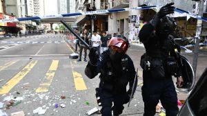 Maskerad polisman med batong i Hongkong.