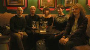 Viisi Withnail & I -elokuvan fania kokoontuneena ravintolapöydän ympärille.