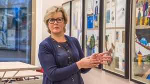 Carola Wiksten står vid konstverk i skolmatsal
