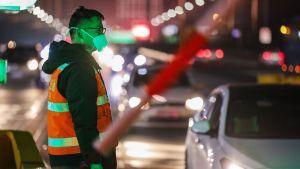 Person med munskydd står vid gata.