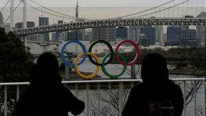 Två personer står och tittar på de olympiska ringarna i Tokyo