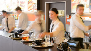 Restauranganställda bakom bardisk med koppar och fat.