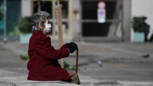En kvinna i skyddsmask satt i centrum av ett rätt folktomt Milano på söndagen.