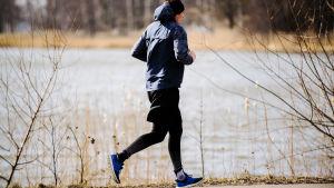 Kuvassa nuori mies juoksee meren rannassa.