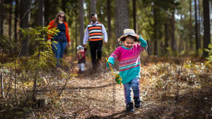 Rezzakuzzamanin perheen vanhempi lapsi juoksee metsäpolulla. Muu perhe kävelee perässä.