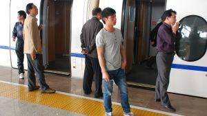 Tågpassagerare på rökpaus vid uppehåll på en station.