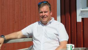 En man med vit skjorta och solglasögon uppe vid hårfästet sitter och kisar mot soeln en solig sommardag med knallblå himmel. Han har en röd fiskebod i bakgrunden. Sitter vid bodens altan.
