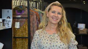 Kvinna i klädbutik med färggranna plagg.