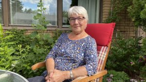 Ann-Mari Svahn sitter i en trädgårdsstol med växter och en gul tegelfasad i bakgrunden.