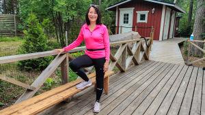 En kvinna står och lutar benet mot ett träräck med ena benet på en träbänk.