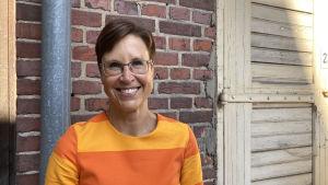 En kvinna med kort hår, glasögon och orangerandig tunika.