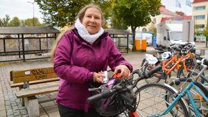 En kvinna som står bredvid sin cykel och visar upp två cykellyktor.