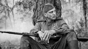En soldat sitter under ett stort träd med begävert vilande på knäna.