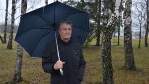 Äldre man står med paraply bland träden.