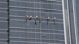 Sex arbetare med hjälm står på en ställning på en hög glasklädd fasad.