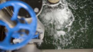 Bild på vattenrening. Vatten rör sig i en bassäng i ett reningsverk så det bildas vitt skum.
