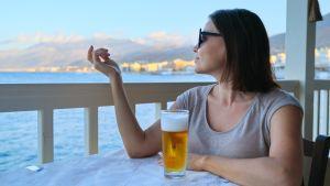 Kvinna sitter på uteservering vid blått hav med öl framför sig