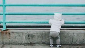 Pieni lapsi nojailee sillan kaiteeseen.