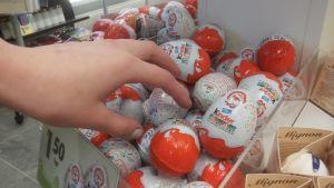 En hand som plockar chokladägg från en butikshyllan.