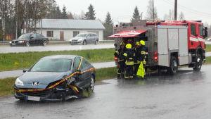 En krockad bil och räddningspersonal på plats.