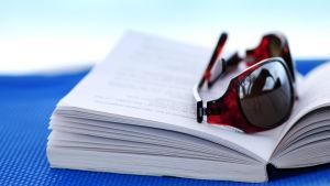 Ett par solglasögon ligger på en öppen bok.