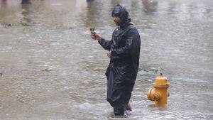 En man står och vadar i knähögt vatten på en gata i Miami.