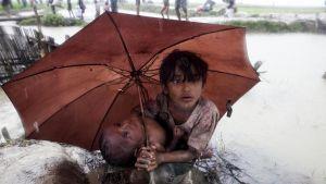 En rohingyaflicka skyddar sin lillasyster med paraply från regnet