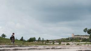 Kvinna promenerar genom grönområde med klippor och en del av ett gammalt fort i bakgrunden. På himlen hopar sig mörka moln.