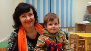 Svetlana i orange scark och blå klänning med sin son i famnen. Sonen håller en transformersfigur i handen