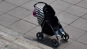 En tom barnvagn med kläder som hänger över styrstången.