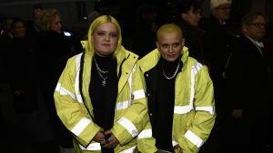 Två kvinnor i gula reflexjackor