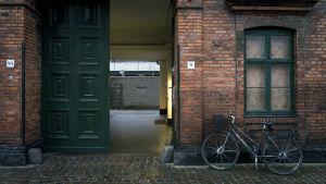 Tegelbyggnad med grön port och en cykel parkerad intill väggen.
