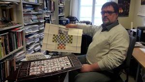 Derek Fewster håller upp ett brädspel i sitt arbetsrum.