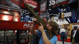 Pojke prövar ett gevär vid NRA:s kongress 2013 i Texas.