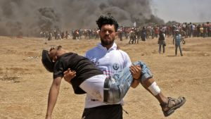En palestinier bär bort sin sårade kamrat från gränsstängslet i Gaza.