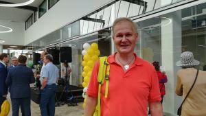 Besökare Marko Ranne var glad över att köpcentrumet äntligen har öppnat. Han står inne i köpcentrumet med ballonger i bakgrunden.