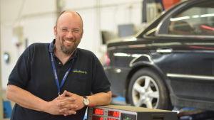 henrik weiner står lutad mot en avgasmätare i en besiktningshall. i bakgrunden finns en mörkblå bil.