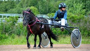 Maximilian kör med sin ponny på travbanan