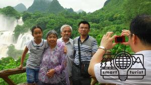 En man fotograferar en familj med vattenfall i bakgrunden.