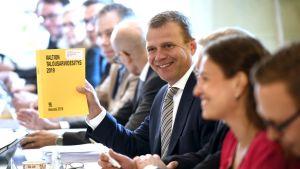 Petteri Orpo håller leende upp finansministeriets budgetförslag, en gul bok