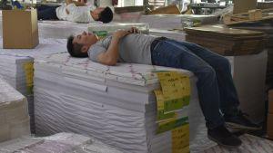 En arbetare ligger på en hög av tryckeriprodukter och sover med benen dinglande