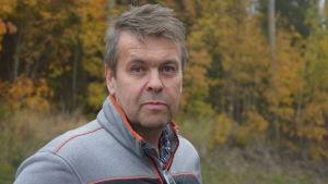 en man i grå-orange kläder ser in i kameran. Bakom höstgula och -röda lövträd.