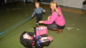 Stephanie Grönroos hjälper sonen Hampus med kläderna. Dottern Hilma i bilstol.