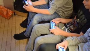 ungdomar som sitter i en soffa och tittar på sina mobiltelefoner. Man ser inte ungdomarnas ansikten.