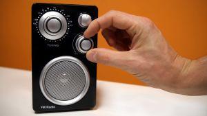 Mies säätää radion äänenvoimakkuutta