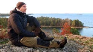 Panu Kunttu sitter på Glasberget och ser ut över havet. Han är ordentligt påklädd med vantar och mössa.