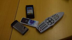 Några icke riktiga mobiltelefoner (leksaker) och en fjärrkontroll till tv på ett bord.