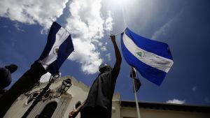 Man håller i Nivaraguas flagga under demonstrationer mot president Ortega