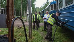 Neljä henkilöä keltaisissa liiveissä, yksi heistä pitää dieselletkua, jonka pää on kiinni sinisessä junavaunussa.