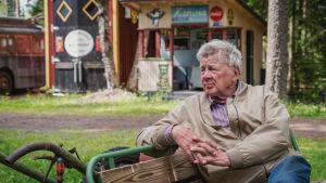 Matti Järvenpää istuu penkillä luomassaan Rautapuistossa.